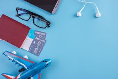 Plane, air tickets, passport, glasses and phone with headphones on a blue background. Concept of preparing for travel. Plane, air tickets, passport, glasses and royalty free stock photography