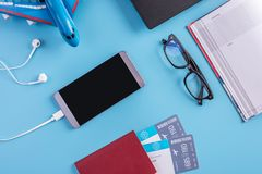 Plane, air tickets, passport, notebook and phone with headphones on blue background. The concept of planning for travel. Plane, air tickets, passport, notebook royalty free stock photography