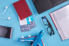 Plane, air tickets, passport, notebook and phone with headphones on blue background. The concept of planning for travel. Plane, air tickets, passport, notebook stock photography