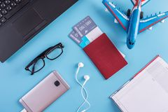 Plane, air tickets, passport, notebook and phone with headphones on blue background. The concept of planning for travel. Plane, air tickets, passport, notebook royalty free stock photos