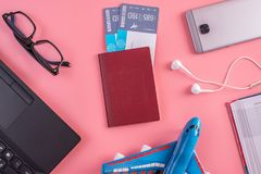 Plane, air tickets, passport, notebook and phone with glasses on pink background. The concept of planning for travel. Plane, air tickets, passport, notebook and royalty free stock image