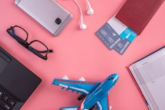 Plane, air tickets, passport, notebook and phone with headphones on pink background. The concept of planning for travel. Plane, air tickets, passport, notebook royalty free stock images