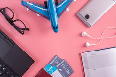 Plane, air tickets, passport, notebook and phone with glasses on pink background. The concept of planning for travel. Plane, air tickets, passport, notebook and stock photography