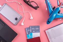 Plane, air tickets, passport, notebook and phone with headphones on pink background. The concept of preparing for travel. Plane, air tickets, passport, notebook royalty free stock image
