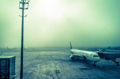 The plane at the airport in the fog Stock Photo