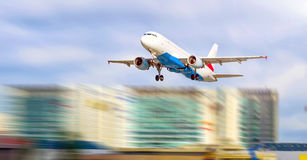 Plane at the airport takes off against the background of the city and skyscrapers royalty free stock photo