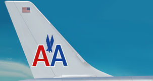 Plane of American Airlines company. Airplane with the symbol (logo) of American Airlines company on the tail. Beautiful blue sky area is free for your text Royalty Free Stock Photo