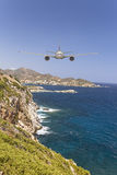 Plane approaching  head-on an island ready to land. Royalty Free Stock Photos