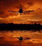 The plane on a background of the sky. Aircraft flying over water and the sunset Stock Images