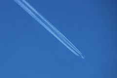 Plane in Blue Sky. Aeroplane flying through clear blue sky with vapour trails Royalty Free Stock Image