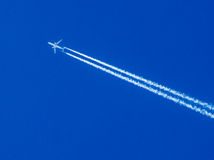 Plane in Blue Sky. Aeroplane flying through clear blue sky with vapour trails Royalty Free Stock Images