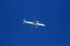 The plane in the bright blue sky Stock Photos