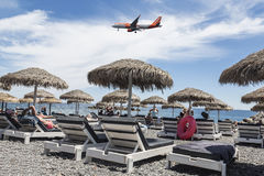 Plane of British low-cost airline flies over the beach in Kamari, Santorini Stock Photos