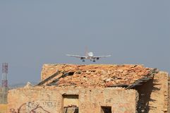 A plane can be seen through the heat haze on its final approach. A holiday jet on its final approach to Alicante airport. An old ruin stands next to the runway Stock Photo