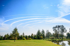Plane circling on blue sky Stock Images