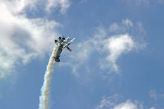 Plane climbs into loop - Wing walker. Airplane at airshow going vertical for a loop with a man standing on the top wing royalty free stock photo