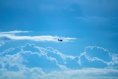 Plane and clouds. Small commuter plane flying against a cloudy sky Royalty Free Stock Images