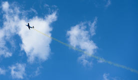 Plane with colorful trail in the sky Stock Photography