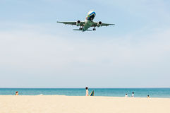 Plane come in the land with some people. Phuket,Thailand - February 24, 2016: beach near the airport, plane come in the land with some people and blue sea and Stock Photography