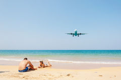 Plane come in the land with some people. Phuket,Thailand - March 10, 2016: Beach near the airport, Plane come in the land with some people and blue sea and white Stock Photo