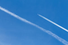Plane and contrails in blue sky. A plane creates a contrail as it flies throungh clear blue sky Royalty Free Stock Photo