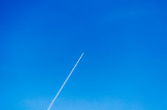 Plane with contrails in the sky. Aircraft leaving contrails in a cloudless sky Royalty Free Stock Photography