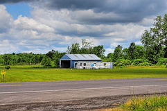Plane at country airport. A view across a road and field to a private airplane parked beside a small hangar at a country airport Stock Images