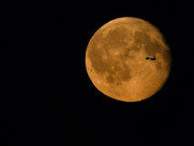 Plane crossing moon Royalty Free Stock Photos