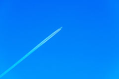 Plane at cruising altitude, airplane with chemtrails on blue sky Royalty Free Stock Photo