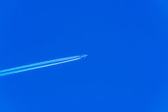 Plane at cruising altitude, airplane with chemtrails on blue sky Stock Photos