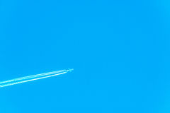 Plane at cruising altitude, airplane with chemtrails on blue sky Royalty Free Stock Image