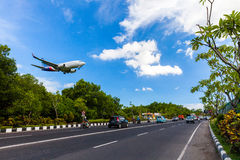 Plane danger landing near road on the tropical island Bali, Ngurah Rai Airport, Tuban, Badung Regency, Bali, Indonesia Stock Photography