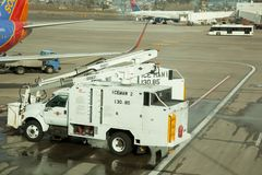 Plane De-Icing Truck. A deicing truck stands ready after a freezing night on a runway with a Delta and Southwest plane in the background Royalty Free Stock Photos