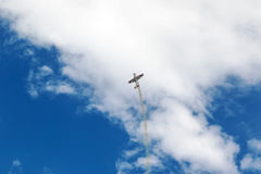 Plane doing tricks in the sky. Plane is flying up the rear exhaust white smoke stock image