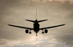 Plane in dramatic evening sky. Airbus approaching to the airport, landing gear down royalty free stock photography