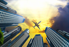 Plane encircled by buildings. Plane soaring high in the sky encircled by skyscrapers Stock Images