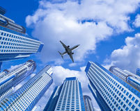 Plane encircled by buildings. Plane soaring high in the sky encircled by skyscrapers Stock Photos