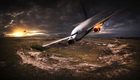 Plane with engine on fire about to crash. White plane with engine on fire about to crash in the landscape Stock Photo