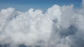 Plane enters a mass of white clouds. View from the airplane window. Plane enters a mass of white clouds from blue sky. View from the airplane window stock video footage