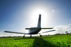 Plane on field. Small plane on field of vivid green grass royalty free stock photos