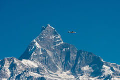 Plane and the Fishtail. A small plane passes by the famous mountain of Nepal, Fishtail Stock Photography