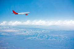 Plane flaying on the top of the mountains Stock Photo