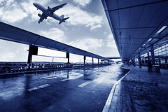 A plane flew over the Shanghai airport building Royalty Free Stock Images