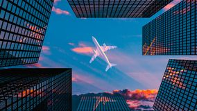 The plane flies above skyscrapers on the blue sky background. Bottom view of airplane above city on the evening sky backdrop Royalty Free Stock Photos