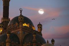 The plane flies against the backdrop of the moon, mosque Royalty Free Stock Photography