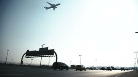The plane flies low over a busy highway with cars. stock video footage