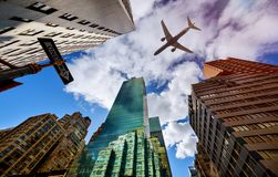 Plane flies low over the New York City Manhattan Skyline USA. Plane flies low over the New York City Manhattan Skyline, USA colorful sunset airplane architecture royalty free stock images
