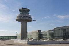 A plane flies next to the control tower at Barcelona Airport, Sp Stock Photo