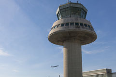 A plane flies next to the control tower at Barcelona Airport, Sp Royalty Free Stock Image