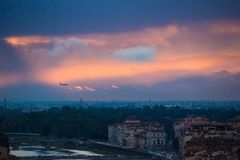 The plane flies over Florence in the evening. Beautiful dramatic sunset over Florence, Italy.  royalty free stock image